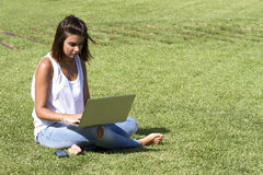 Sitta på ett gräs Arkivbild