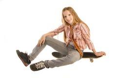 Sitta på skateboarden Fotografering för Bildbyråer