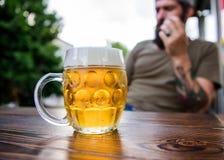 Sitta runt om att dricka öl Hipster som dricker öl i stång Skäggig man som dricker alkohol i bar Brutal man som har arkivbild