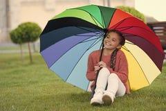 Sitta under paraplyet och ha gyckel Den lilla flickan parkerar in v?ntande p? regn F?rgglat paraply som begrepp av lycka fotografering för bildbyråer