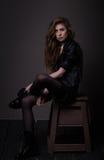 Sittande attraktiv kvinna i svart klänning- och läderomslag Royaltyfri Bild