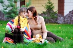 sittande barn för dotterlawnmoder royaltyfri fotografi