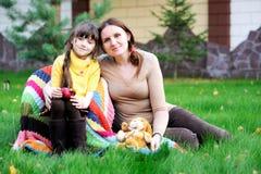 sittande barn för dotterlawnmoder arkivbild