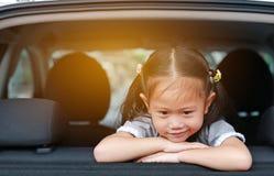 Sittande halvkombid?rr f?r litet asiatiskt barn av bilen med att se ut royaltyfria foton