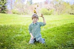 Sittande kasta för pojke upp nya valda blommor royaltyfria foton
