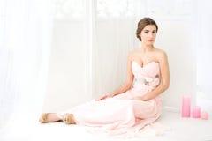sittande kvinna för golv Brud i rosa färgklänning Royaltyfri Fotografi