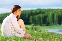 sittande kvinnabarn för gräs Arkivbild