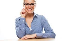 Sittande lycklig benägenhet för kontorsflicka på tabellen royaltyfri foto