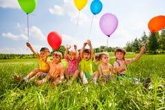 Sittande roliga ungar med ballonger i luften Arkivbild