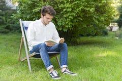 Sittande skäggig ung vuxen läsning en bok i trädgården Royaltyfri Bild