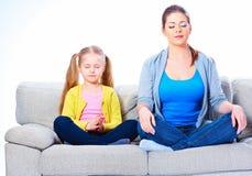 sittande sofa för dottermoder göra kvinnayoga Fotografering för Bildbyråer