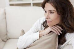 Sittande tänka för brunettkvinna hemma på sofaen Arkivfoto