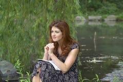 sittande tänka för flickapark royaltyfri foto