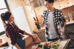 Sittande tabell för kvinna som ser maken Man som rymmer exponeringsglas och vin royaltyfri foto