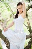sittande white för brunettklänning arkivbilder