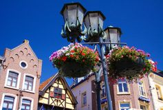 SITTARD, NETHERLANDS - JUIN 29. 2019: Low angle view on street lamps decorated with flower baskets against blue sky with medieval royalty free stock images
