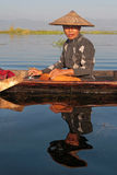 Sitted fisherman and reflection on waters of Inle Lake Royalty Free Stock Image