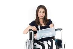 Sitter den asiatiska kvinnan för den brutna armen med armremmen som sponsras i hennes händer arkivfoton