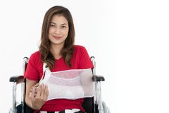Sitter den asiatiska kvinnan för den brutna armen med armremmen som sponsras i hennes händer fotografering för bildbyråer