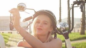 Sitter den bärande hjälmen för unga flickan och skyddande exponeringsglas nära den elektriska cykeln stock video