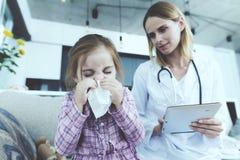 Sitter den blåsa näsan för den sjuka ungen och nära kvinnlig doktor fotografering för bildbyråer