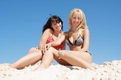 sitter den blonda brunetten för strand royaltyfri fotografi