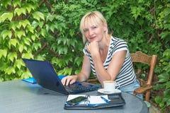 Sitter den blonda mitt åldrades kvinnan i utomhus- kontor Arkivbilder