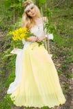 SITTER DEN BLONDA MODELLEN för den härliga unga sinnliga kvinnan i fantastisk klänning på en gunga inställd från TRÄDET Royaltyfri Fotografi
