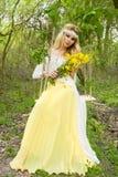 SITTER DEN BLONDA MODELLEN för den härliga unga sinnliga kvinnan i fantastisk klänning på en gunga inställd från TRÄDET Arkivbilder