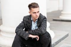 Sitter den eleganta unga mannen för affären i ett klassiskt plädomslag i en skjorta i jeans med en frisyr på våren dag arkivbild
