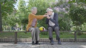 Sitter den gamla kvinnan f?r st?enden med buketten av gula blommor i b?nken med en gamal man, och rymma h?nder i parkera anbud stock video