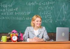 Sitter den gladlynta angenäma kvinnautbildaren för läraren tabellklassrumarbete med bärbara datorn Online-jobbbräden eller karriä royaltyfria foton