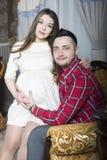Sitter den gravida flickan för barn på en stol i armarna av hennes hus Royaltyfria Bilder