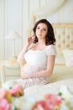 Sitter den gravida unga kvinnan för brunetten i en härlig inre med rosor Arkivbild