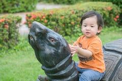 Sitter den gulliga asiatiska ungen för closeupen på sköldpaddastatyn i parkerabackgrouen fotografering för bildbyråer