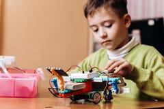 Sitter den iklädda gröna tröjan för pojken på skrivbordet med datoren och blickar på roboten som han gjorde från det robotic arkivbild