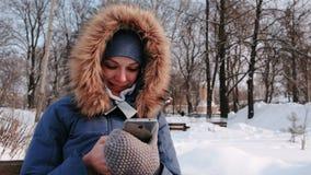 Sitter den lyckliga kvinnan för closeupen på bänk, och bläddra mobiltelefonen i vinter parkera i staden under dagen i snöig stock video