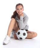 sitter den lyckliga spelare för bollfotbollflickan tonårs- Arkivfoton