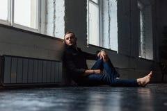 Sitter den stiliga trendiga mannen för ståenden i en svart skjorta på ett trägolv vid fönstret Royaltyfria Foton
