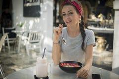 Sitter den unga kvinnan för fotoet i grå klänning på en tabell i det öppna kafét som tycker om semester arkivbilder