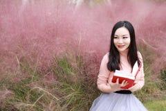 Sitter den utomhus- härliga flickan för den nätta asiatiska kinesiska kvinnan på gräsgräsmatta i parkerar trädgården känner den b royaltyfria foton