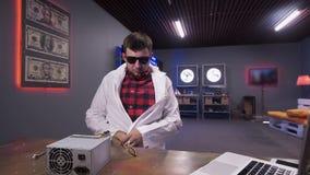 Sitter det bärande vita labblaget för mannen bak skrivbordet med asken av strömförsörjning med kylare lager videofilmer