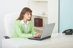 sitter det ljusa kontoret för bärbar dator tabellkvinnan Fotografering för Bildbyråer