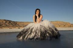 Sitter is för den formella klänningen för kvinnan lutar framåt allvarligt Royaltyfri Bild