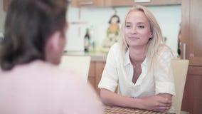 Sitter iklädd vit för den gulliga blonda flickan och för den unga mannen på tabellen i kök stock video