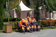 Sitter kommunala arbetare för stad på ett avbrott för bänk för kort, når de har gjort ren stadsgatan i april den soliga dagen arkivfoto
