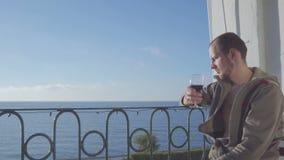 A sitter på balkongen och dricker rött vin på bakgrunden av havet Närbild lager videofilmer