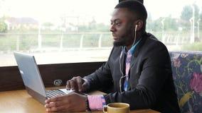 Sitter video pratstund för afro- amerikanska svart mansamtal på datoren i skalm i kafé stock video