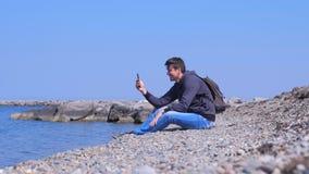 Sitter video pratstund för mansamtal i hans smartphone på havsstenstranden på semester lager videofilmer