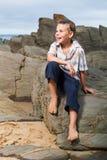 Sittig auf den Felsen Stockfotografie